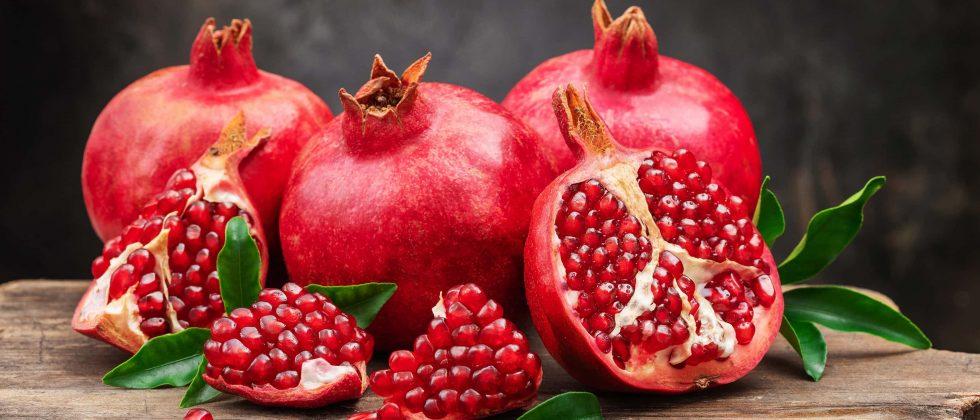 Arrangement of Pomegranates on wooden table