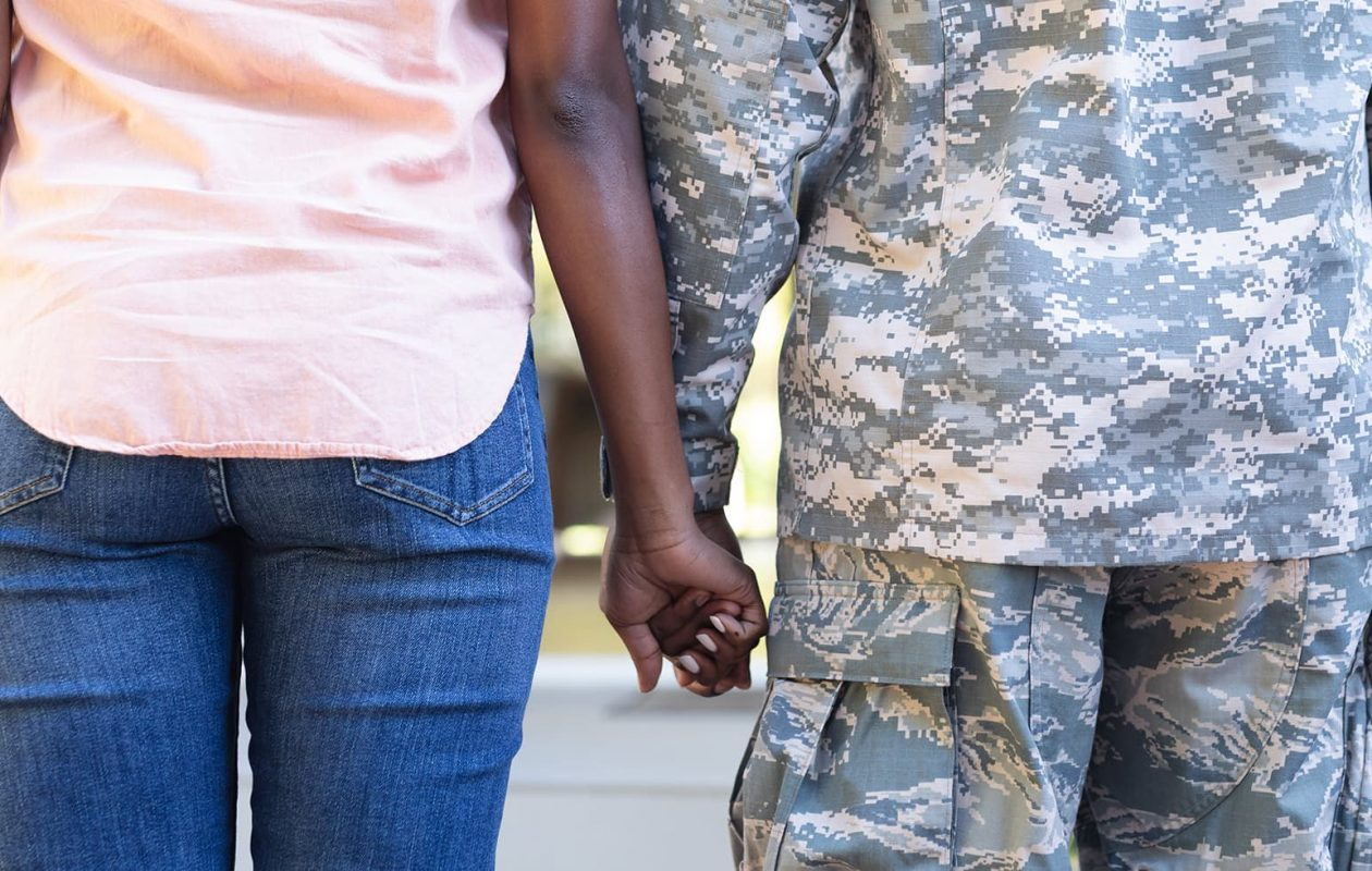 soldier and wife holding hands